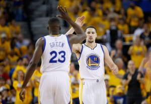 OAKLAND, CA - MAY 01: Klay Thompson #11 of the Golden State Warriors high-fives Draymond Green #23 during the first quarter against the Portland Trail Blazers during Game One of the Western Conference Semifinals for the 2016 NBA Playoffs at ORACLE Arena on May 01, 2016 in Oakland, California. NOTE TO USER: User expressly acknowledges and agrees that, by downloading and or using this photograph, User is consenting to the terms and conditions of the Getty Images License Agreement.