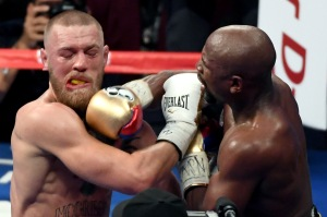 LAS VEGAS, NV - AUGUST 26: Floyd Mayweather Jr. (R) hits Conor McGregor in the ninth round of their super welterweight boxing match at T-Mobile Arena on August 26, 2017 in Las Vegas, Nevada. Mayweather won by 10th-round TKO.