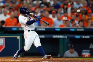 HOUSTON, TX - OCTOBER 05: Jose Altuve #27 of the Houston Astros hits a home run in the fifth inning against the Boston Red Sox during game one of the American League Division Series at Minute Maid Park on October 5, 2017 in Houston, Texas.